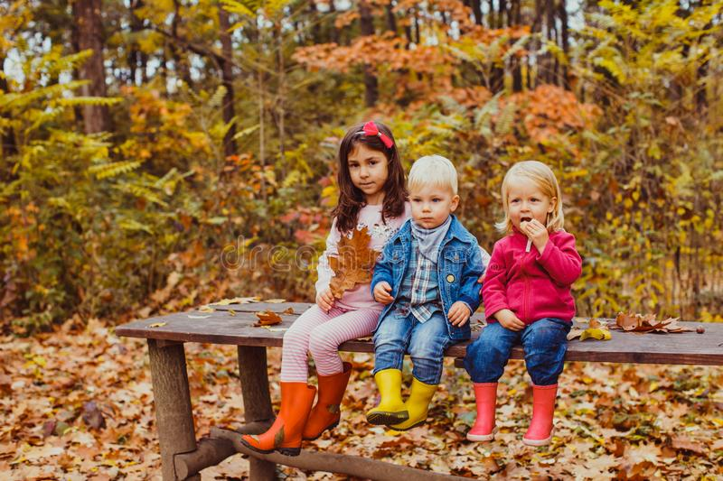 Three kids sitting on the bench and playing royalty free stock photo