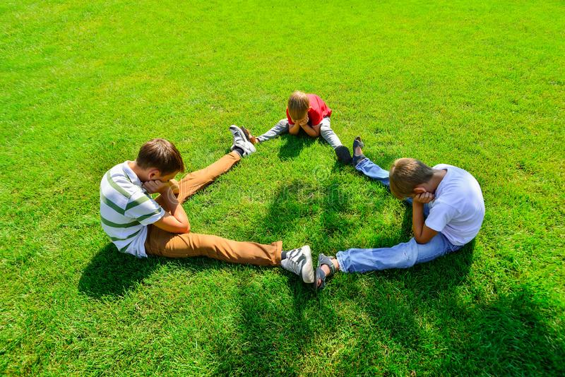 Three kids are sitting on green grass holding hands in a park royalty free stock image