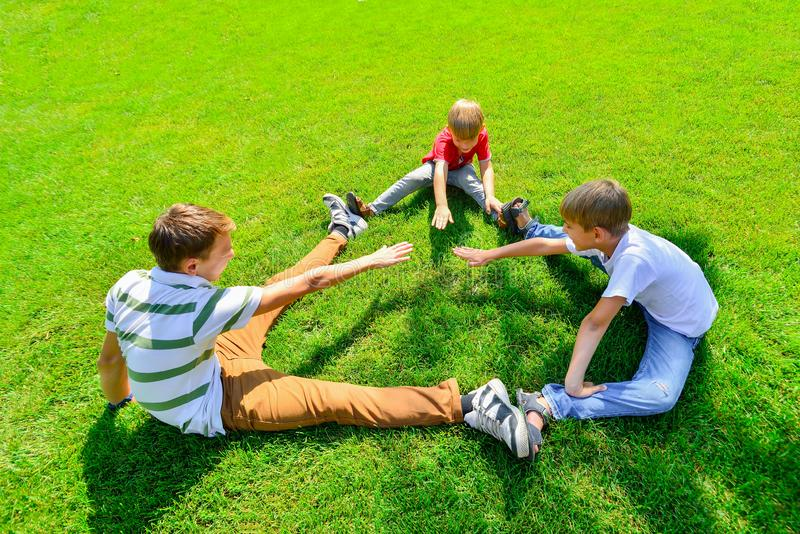 Three kids are sitting on green grass holding hands in a park royalty free stock photo
