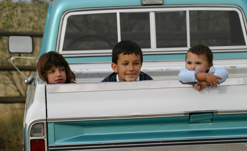 Three Kids in Truck. Three Hispanic American children, each with different expressions, hanging out in the back of an old pick up truck royalty free stock photos