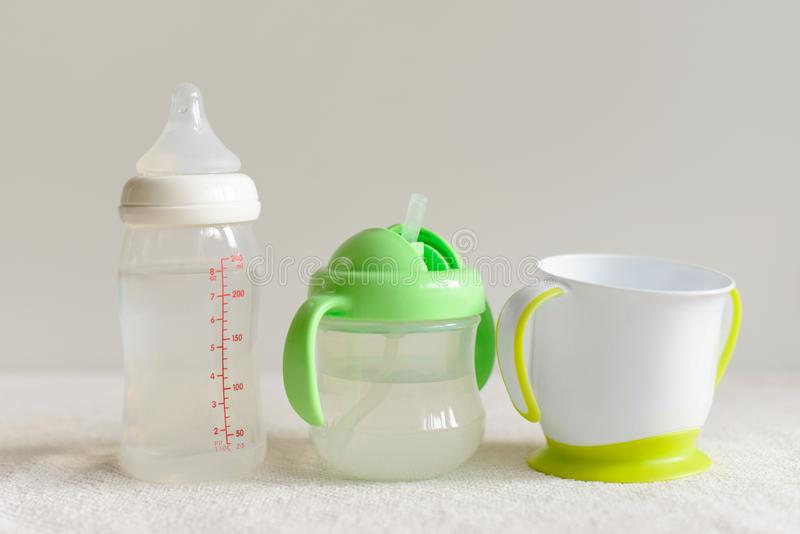 Three kinds of bottles and cups with water for baby. royalty free stock photography
