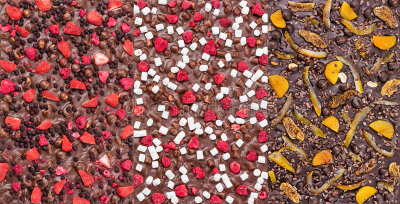 Three kinds of chocolate bars with dried berries, fruit and nuts royalty free stock image