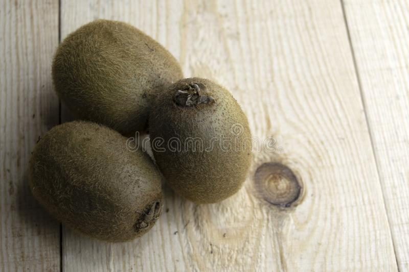 Three kiwis on a wooden table royalty free stock image