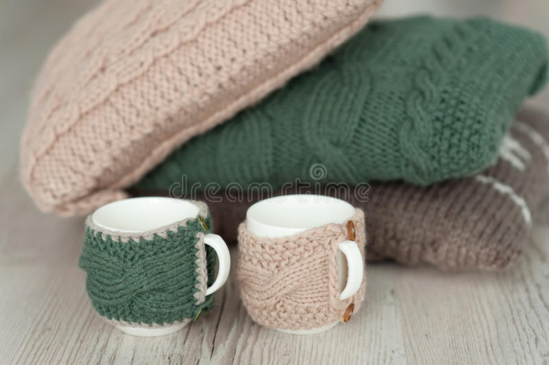 Three knitted pillows and two cups on wooden board background royalty free stock photography