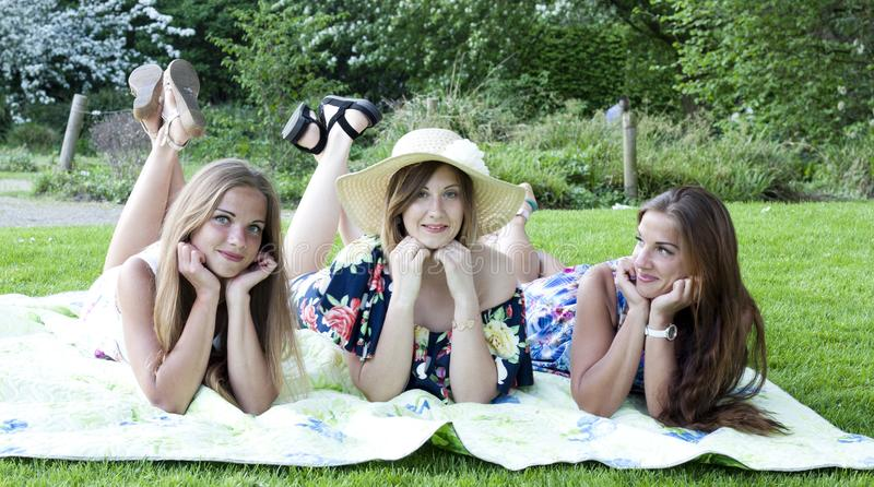 Three ladies in picnic. Laying on blanket. Three beautiful ladies having picnic. Laying on blanket. Legs lifted and crossed. Summer dresses, sun tan, long hair stock images