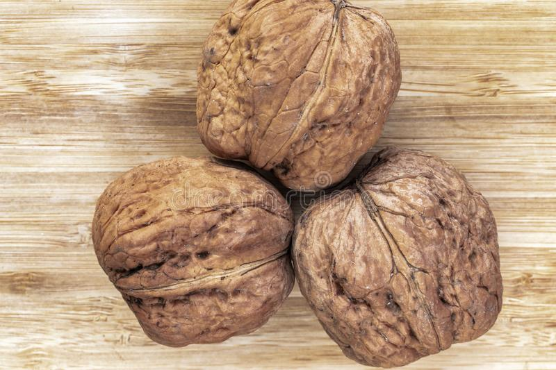 Three large inshell walnuts lie in the center on a brown wooden surface stock image