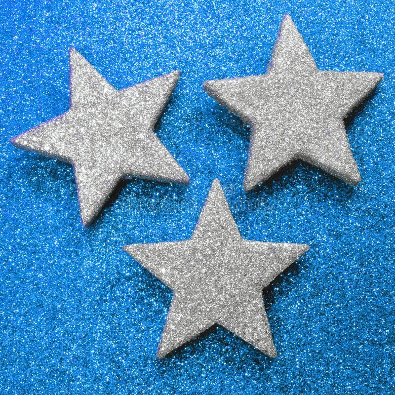 Three large silver stars on bright blue glittery background royalty free stock photo