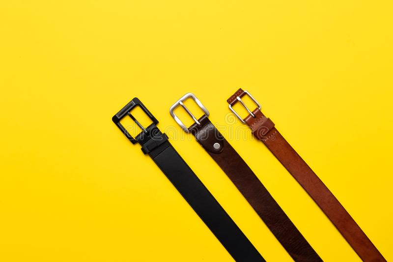Three leather belt for trousers on yellow background. Top view flat lay. Every day style royalty free stock photography