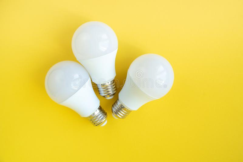 Three LED light bulbs on yellow background. energy saving concept stock photo
