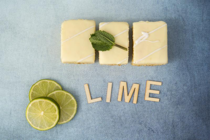 Three lemon and lime cakes with lime slices and the word lime. On a blue background royalty free stock photography