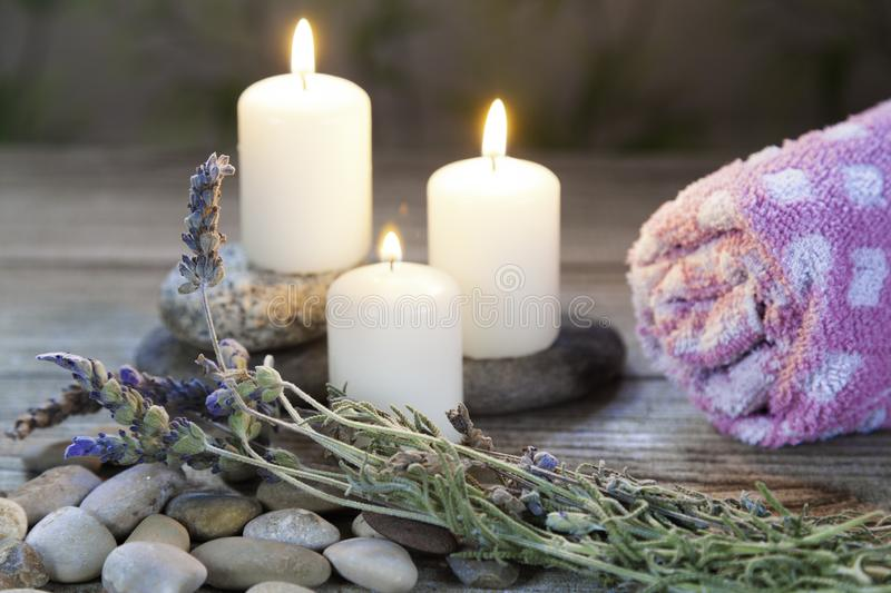 Three lighted candles with lavender and towel on wooden table and herbal background royalty free stock image