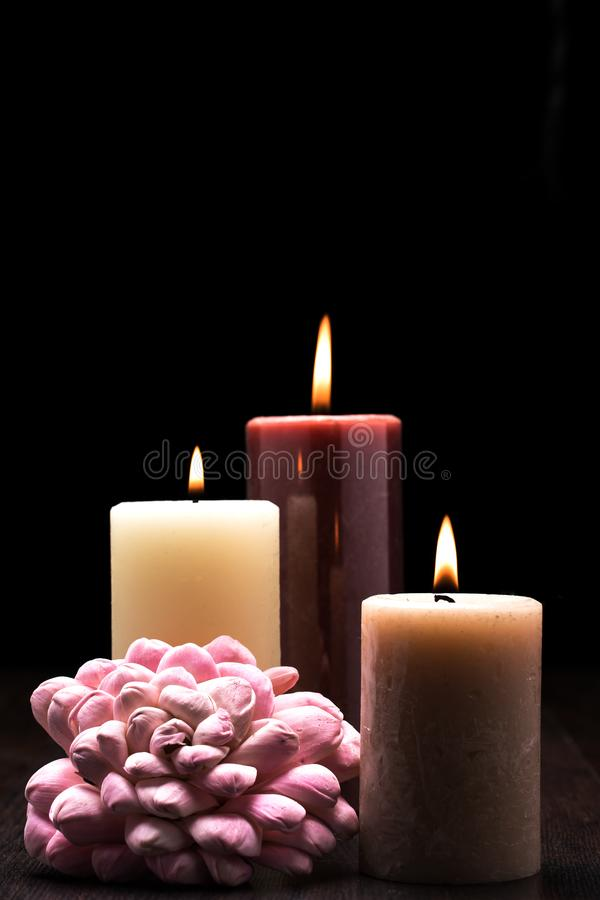 Three lit candles on wooden table with black background and a pink flower arrangment. Rembrandt lighting inspired Christmas scene royalty free stock images