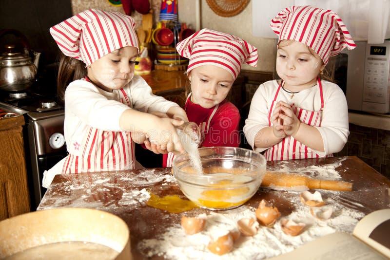 Three little chefs in the kitchen. Three little chefs enjoying in the kitchen making big mess. Little girls making bread in the kitchen royalty free stock photos
