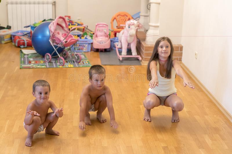 Three little children do exercises. concept of a healthy lifestyle. Little children do sit-ups.  royalty free stock photography