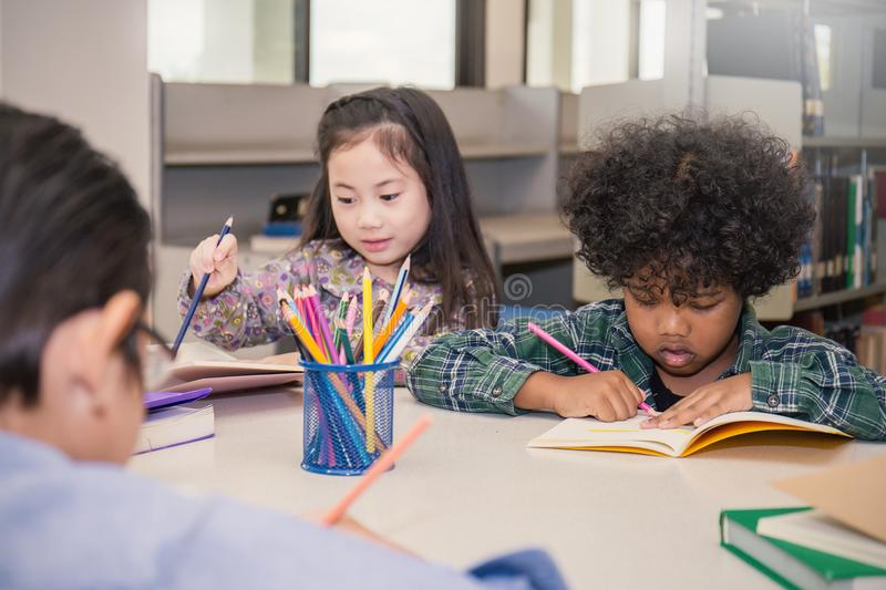 Three little children sitting hand holding pencil and coloring picture. Pupils Studying At Desks In Classroom, three little children sitting hand holding pencil stock images