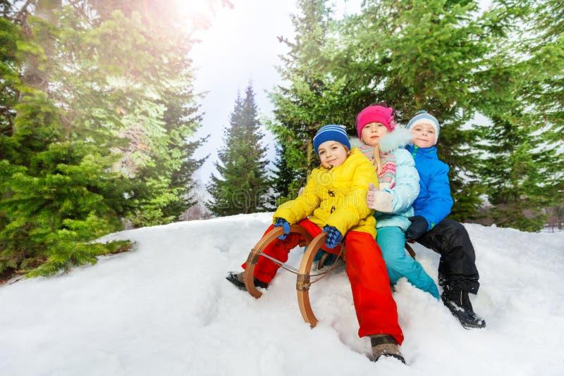 Three little children on sledge in park stock image