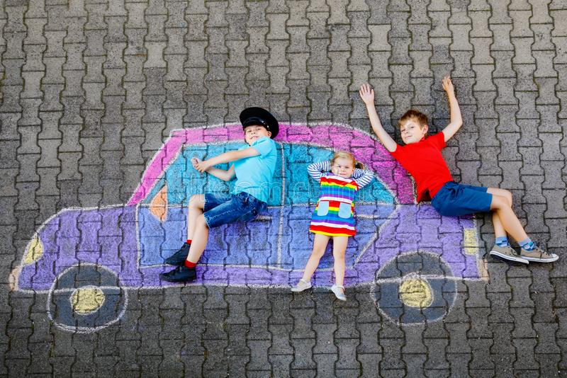 Three little children, two school kids boys and toddler girl having fun with with car picture drawing with colorful. Chalks on asphalt. Siblings painting on royalty free stock photography