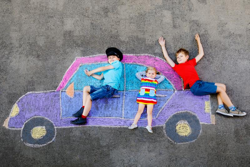 Three little children, two school kids boys and toddler girl having fun with with car picture drawing with colorful. Chalks on asphalt. Siblings painting on stock photos