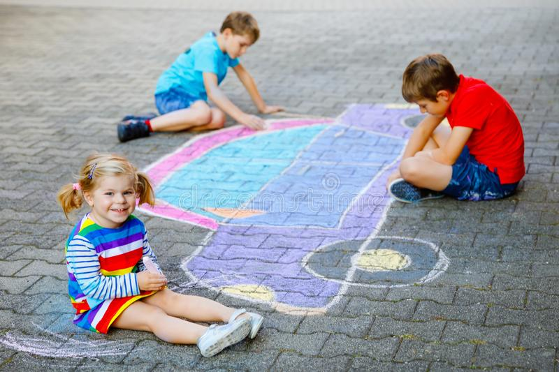 Three little children, two school kids boys and toddler girl having fun with with car picture drawing with colorful. Chalks on asphalt. Siblings painting on royalty free stock images