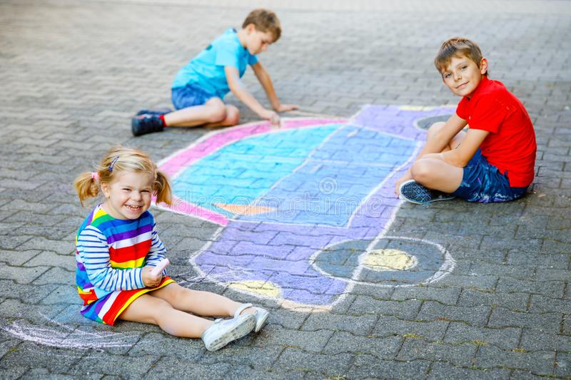 Three little children, two school kids boys and toddler girl having fun with with car picture drawing with colorful. Chalks on asphalt. Siblings painting on royalty free stock image