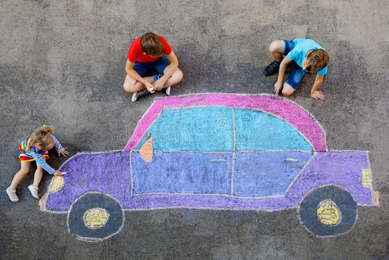 Three little children, two school kids boys and toddler girl having fun with with car picture drawing with colorful. Chalks on asphalt. Siblings painting on royalty free stock photo