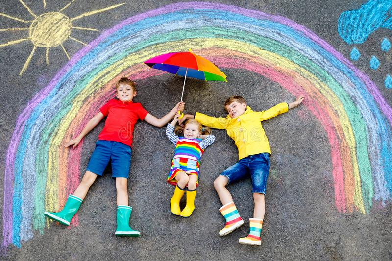 Three little children, two school kids boys and toddler girl having fun with with rainbow picture drawing with colorful. Chalks on asphalt. Siblings in rubber stock photography