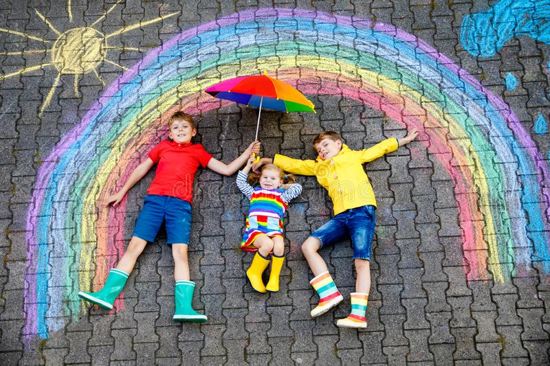 Three little children, two school kids boys and toddler girl having fun with with rainbow picture drawing with colorful. Chalks on asphalt. Siblings in rubber royalty free stock photography