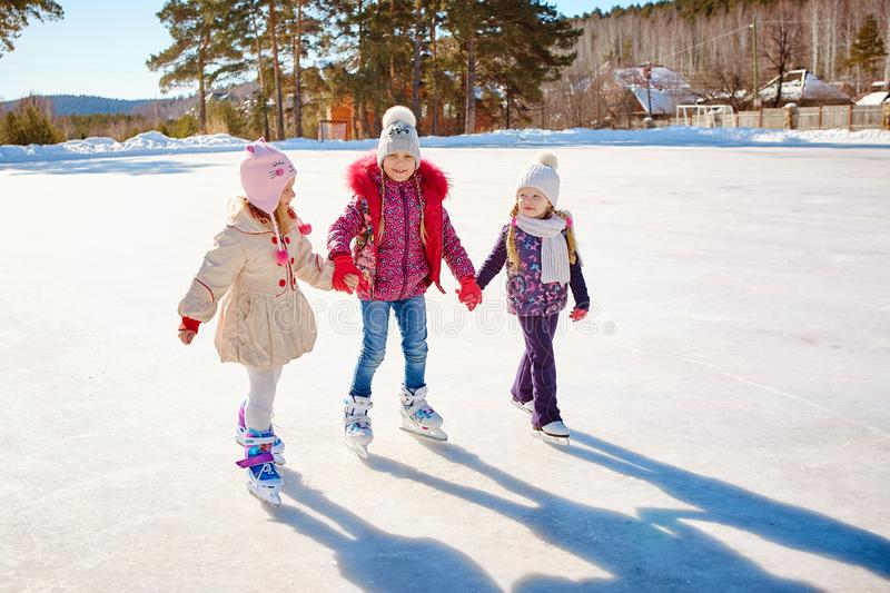 Three little girl friends learn to skate. Outdoor recreation an stock photos