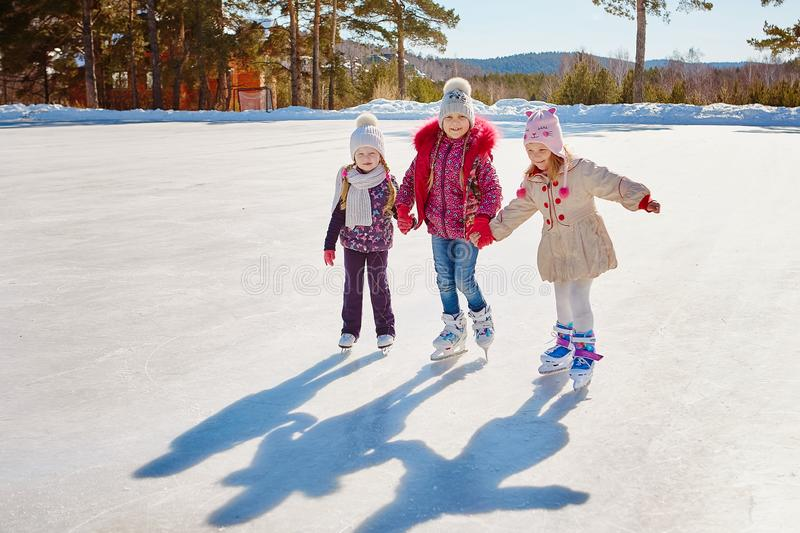 Three little girl friends learn to skate. Outdoor recreation and holidays royalty free stock photos