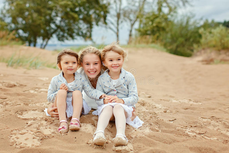 Three little girls are adorable sisters hugging on the background of the sea in windy summer weather royalty free stock photography