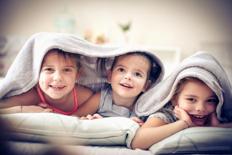 Little girl covered over head. Three little girls in bed covered over head. Space for copy royalty free stock image