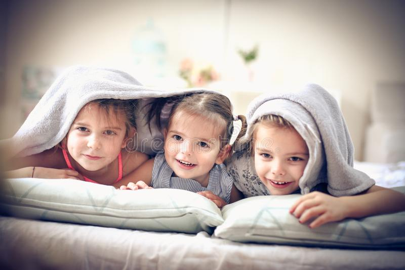 Portrait three little girls. Three little girls in bed covered over head. Space for copy stock photography