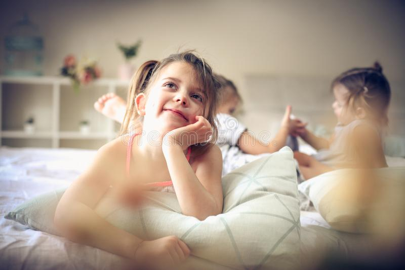 Children memories. Kids in bed. Three little girls in bed. Focus is on little girl. Space for copy stock photos
