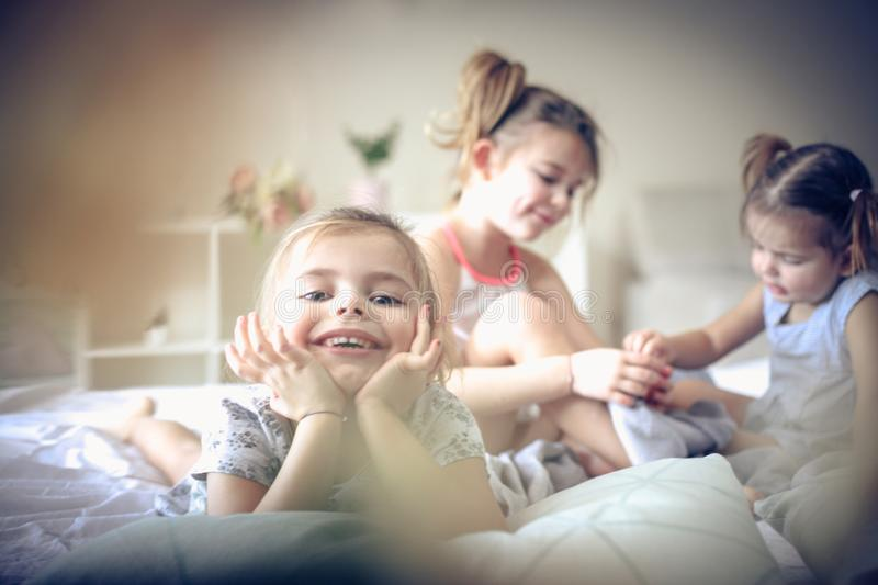 Little girl looking at camera. Three little girls in bed. Focus is on little girl. Space for copy stock images