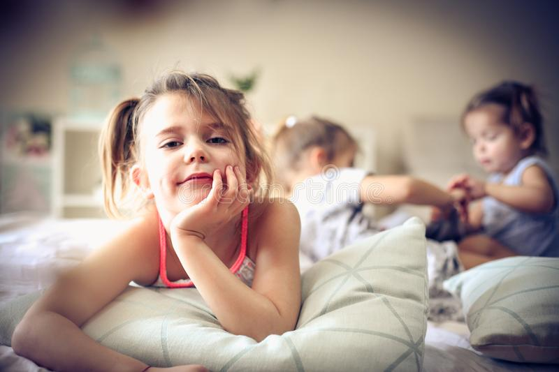 Little girl looking at camera. Three little girls in bed. Focus is on little girl. Space for copy stock photography