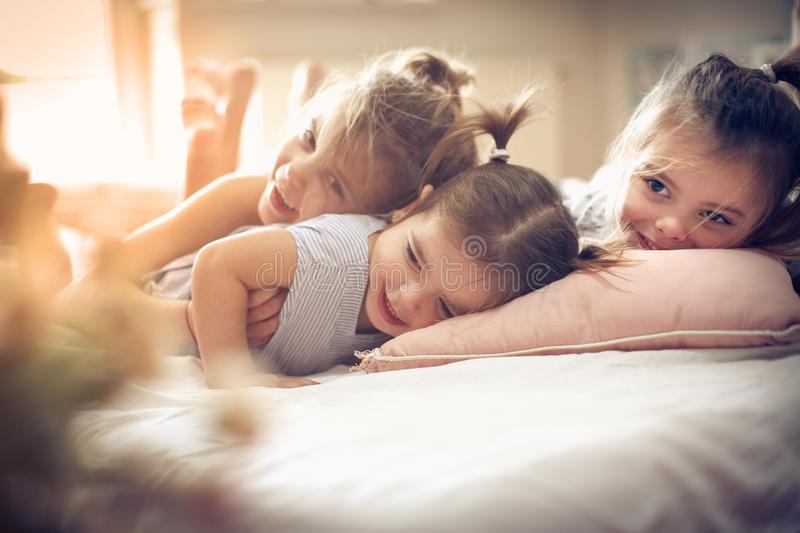 Three little girls in bed. Three little girls lying on bed. Space for copy royalty free stock photo