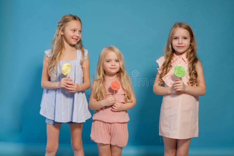 Eat sweet candy lollipop three little girls blonde stock photography