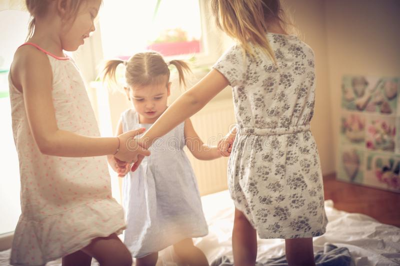 Sunny happy morning. Three little girls dancing in bed. Space for copy royalty free stock photography