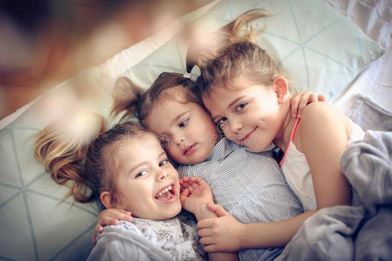 Fun in bed. Three little girls lying in bed and hugging. Space for copy stock photos