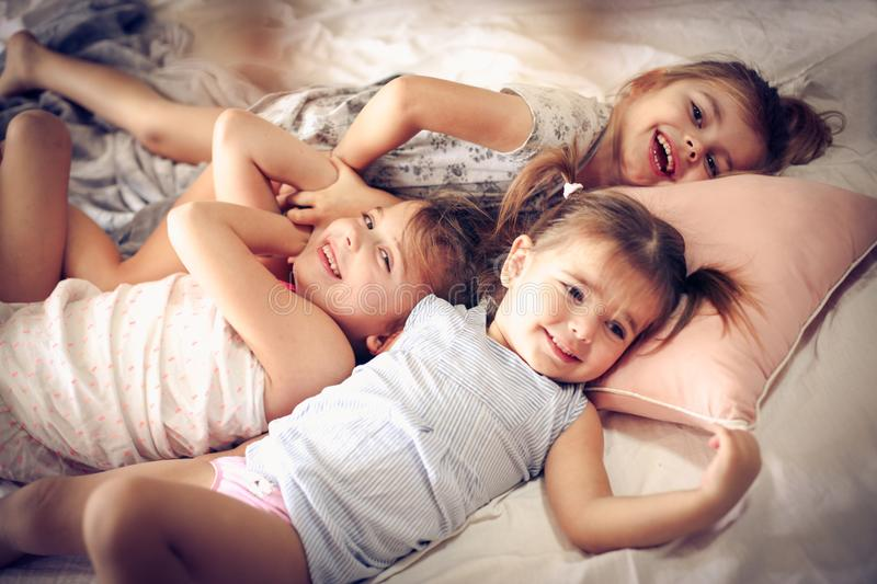 Little sisters in bed. Three little girls lying on bed. Space for copy royalty free stock photos