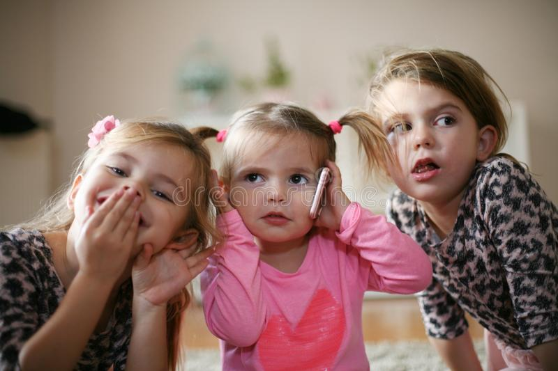 Three little girls with mobile phone. stock photography