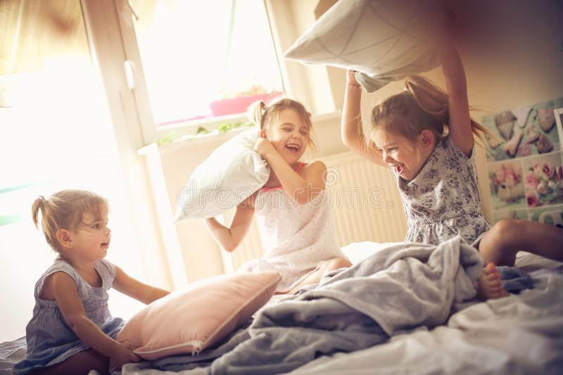 Fight with pillow. Three little girls playing in bed and having fight with pillow. Space for copy royalty free stock photos