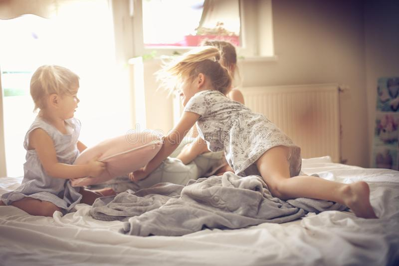 Fun in morning. Three little girls playing in bed and having fight with pillow. Space for copy stock photo
