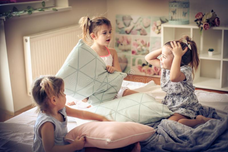 Funny morning. Kids on bed. Three little girls playing in bed and having fight with pillow. Space for copy stock photography