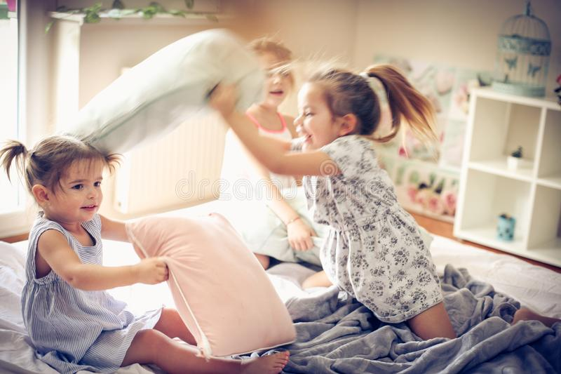 Funny play. Three little girls playing in bed and having fight with pillow. Space for copy stock images