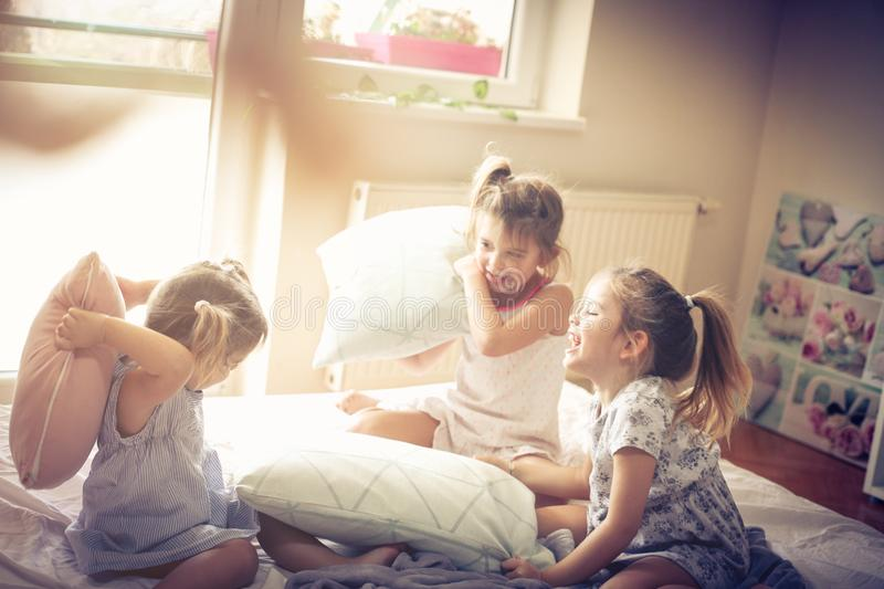 Happy morning. Kids in bed. Three little girls playing in bed and having fight with pillow. Space for copy stock photography