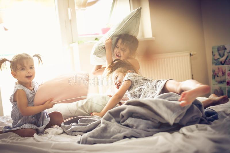 Playful morning. Kids on bed. Three little girls playing in bed and having fight with pillow. Space for copy stock image