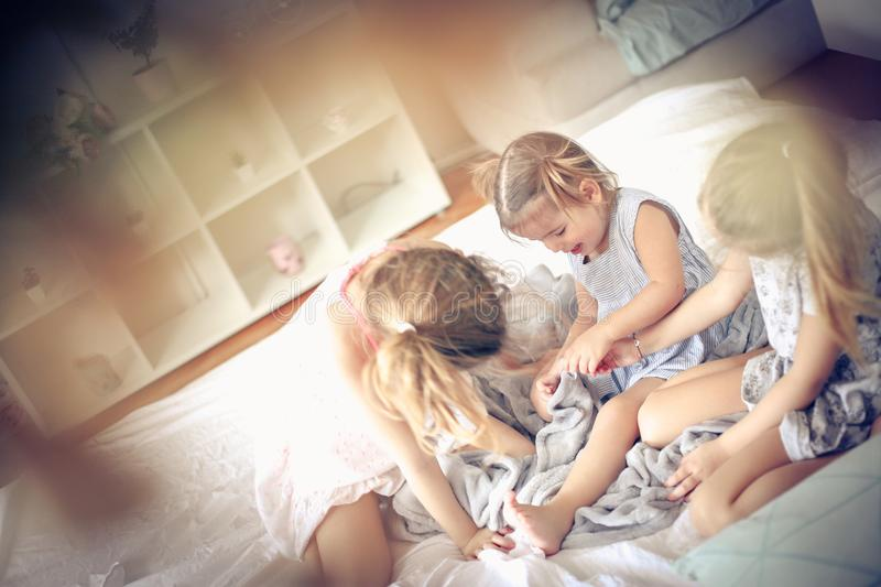 Playing in bed. Three little girls plying in bed. Space for copy stock photography