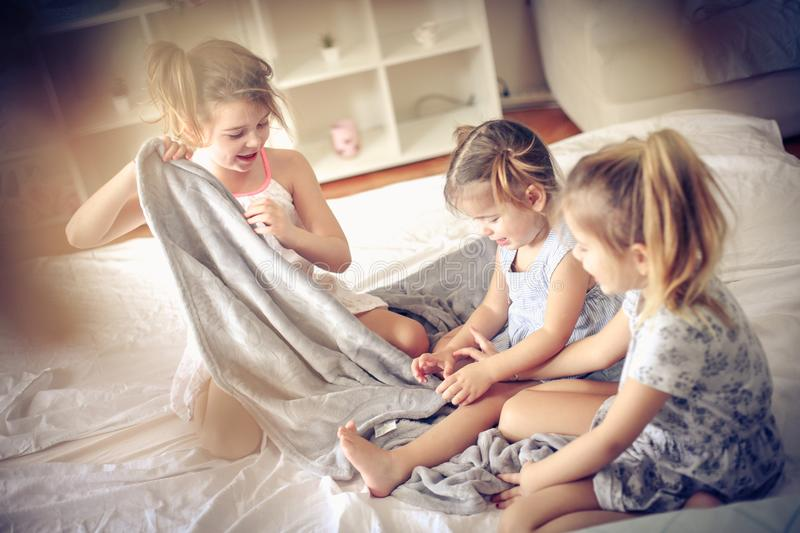 Playing with blanket. Three little girls plying in bed. Space for copy royalty free stock photography
