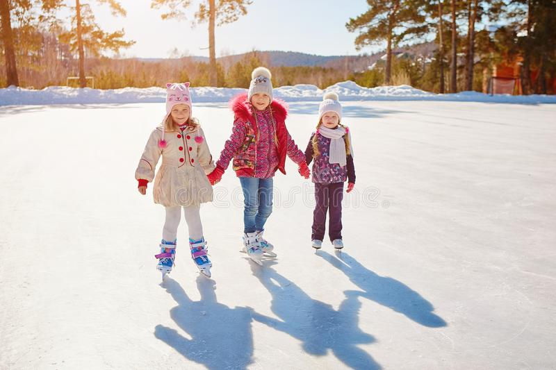 Three little girls skate on the ice. Vacations and holidays in nature stock image
